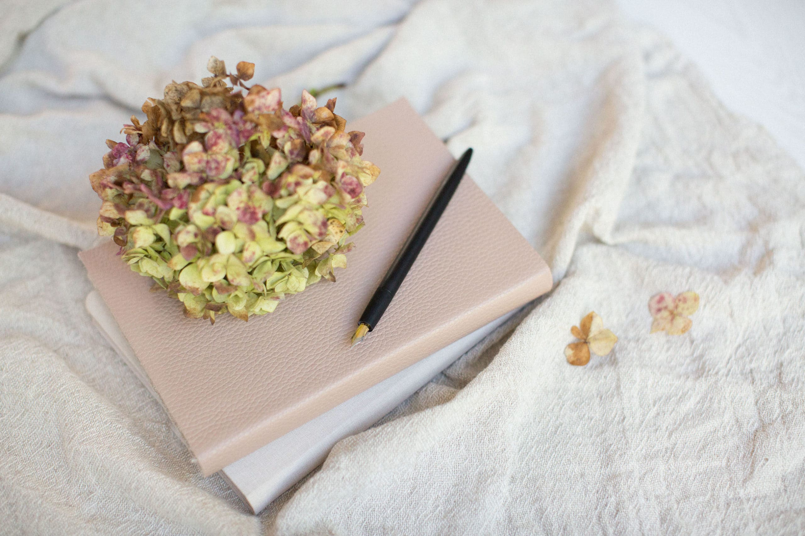 notebook with pen and flower