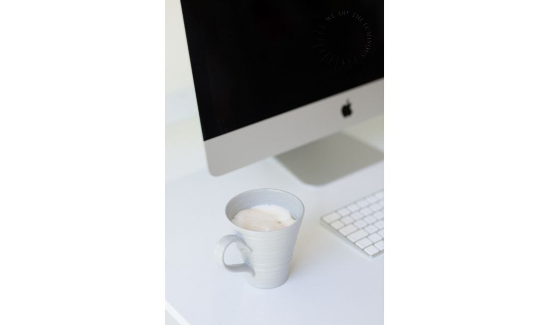cup of coffee next to computer