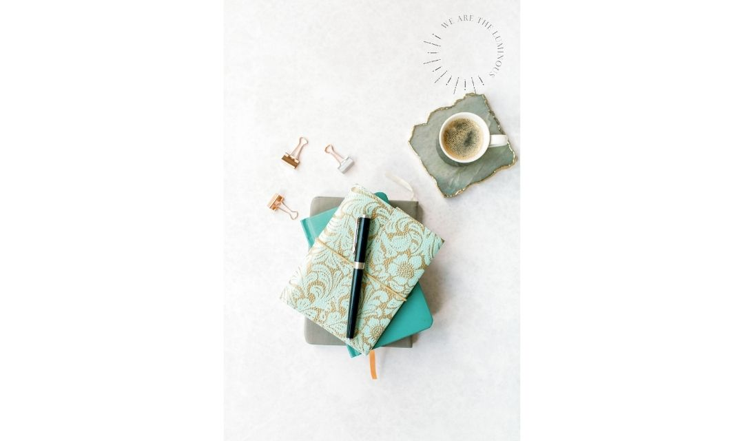 turquoise note book with pen and coffee