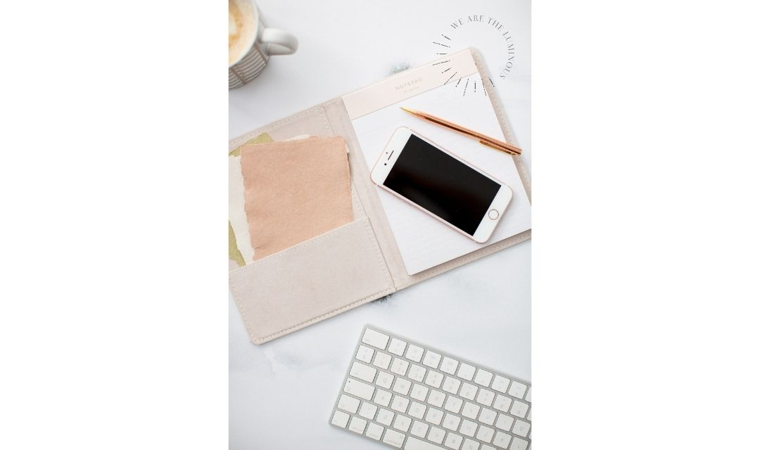 blush notebook with iphone and computer keyboard
