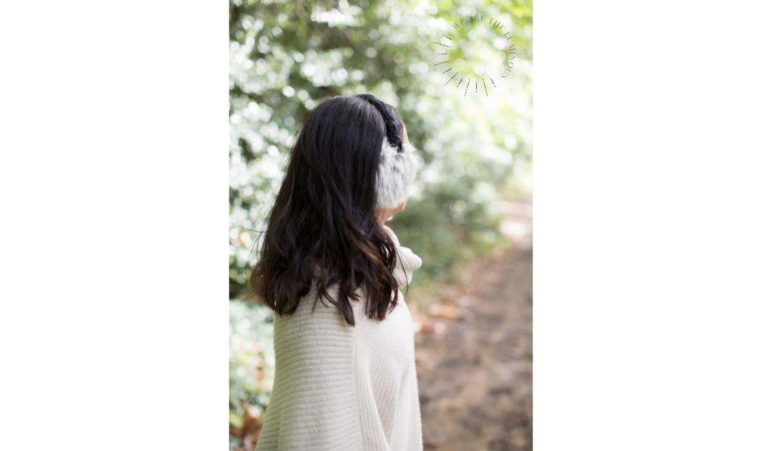 lady wearing ear muffs in the woods