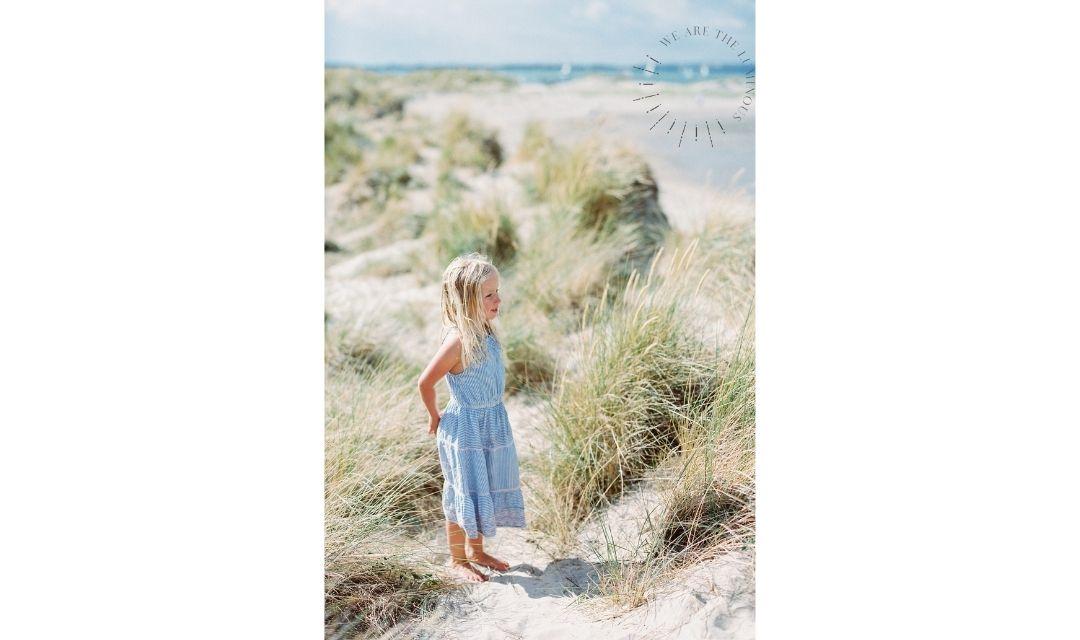 girl standing in sand dunes stock photo