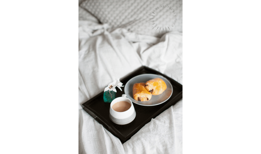 croissant and book in bed stock image