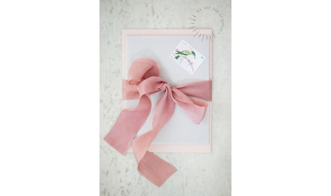 pink ribbon tied round envelope