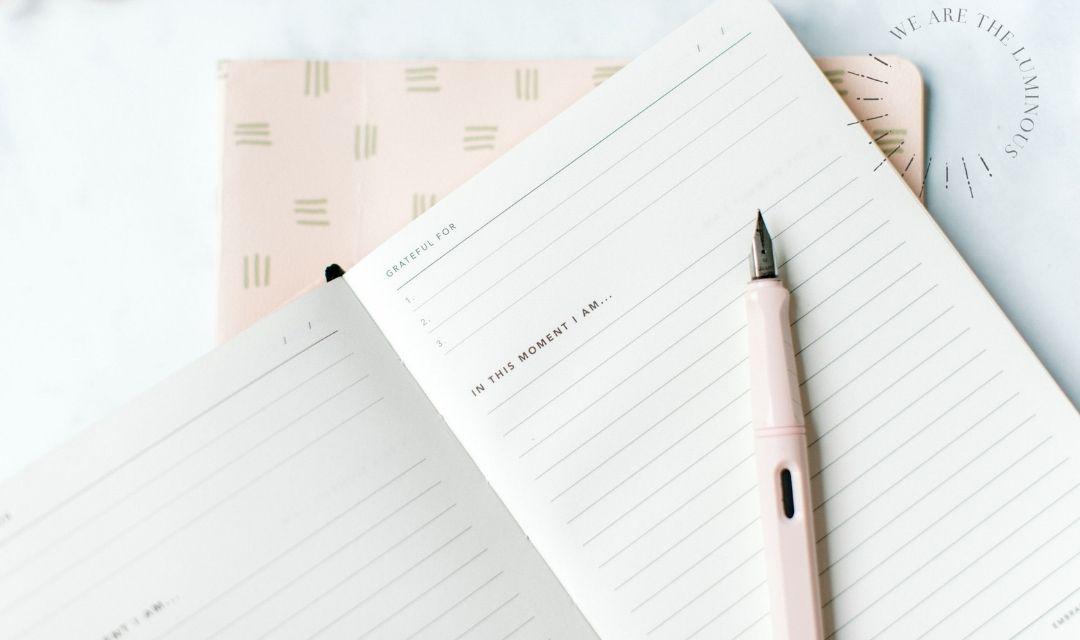 pink pen on gratitude notepad