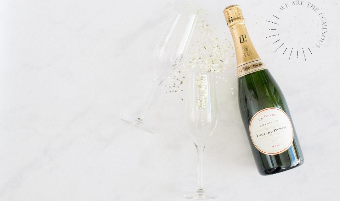 two champagne glasses and bottle of champagne styled stock photography