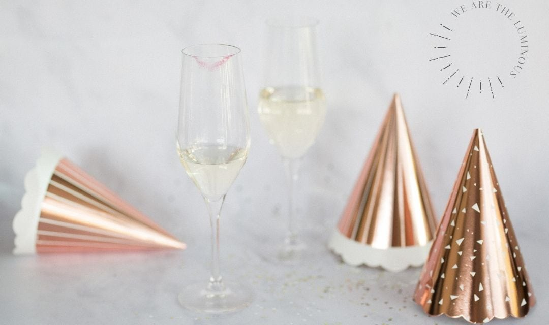 two champagne glasses and party hats