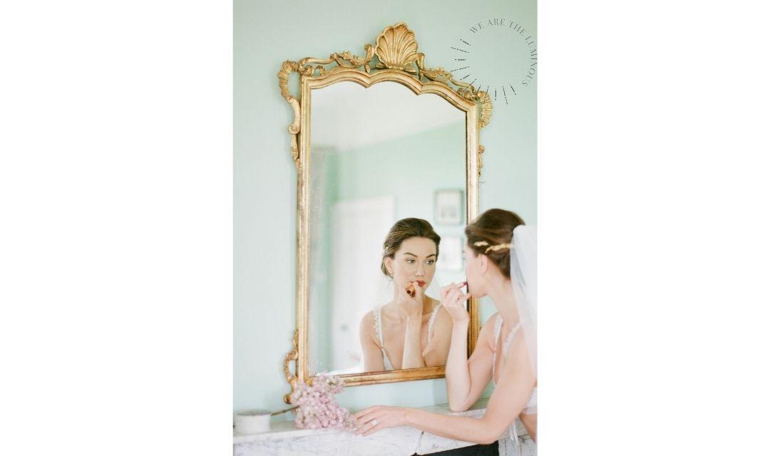 A bride getting ready applying lipstick
